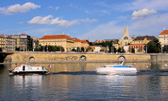 Uferpromenade an der Moldau - zwei Sportboote fahren flussabwärts. Rechts das Kloster Emmaus mit den 1967 errichteten modernen Giebeln (Architekt František M. Černý ); die historischen gotischen Giebel wurden im Krieg zerstört.