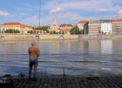 Angler am Ufer der Moldau - am anderen Ufer Promenade und Häuser von Prag.