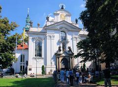 Kloster Strahov - Rückseite der Klosterkirche Mariä Himmelfahrt - Barockkirche; Touristen und Gläubige in der Gartenanlage vor der Kirche.
