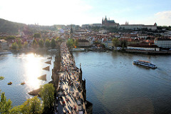 Blick auf die historische Karlsbrücke wurde im 14. Jahrundert errichtet. Sie ist einer der ältesten Steinbrücken Europas. Brücke ist eine der vielen Sehenswürdigkeiten Prags - dicht gedrängt überqueren dort die Touristen zu Fuß die Moldau. Im Hinterg