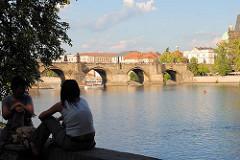 Ufer der Moldau in der tschechischen Hauptstadt Prag - zwei Frauen sitzen im Schatten am Wasser; im Hintergrund überquert die Karlsbrücke den Fluss.
