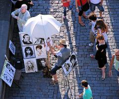 Ein Künstler zeichnet auf der Karlsbrücke Portraits unter einem Sonnenschirm - Pragtouristen sehen ihm bei der Arbeit zu.