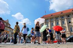 Touristen auf der Burganlage der Prager Burg - Touristen mit Sonnenschirm + blauer Himmel.