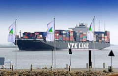 Fahnen mit Stader Logo - Frischer Wind im Norden -  am Stader Sand; 336m lange und knapp 46m breite Containerschiff NYK ORION fährt elbabwärts - der Frachter kann 9040 TEU Container transportieren.