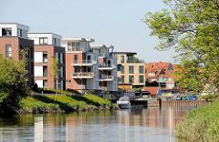 Moderne Wohnungen am Ufer der Schwinge in Stade - Neubauten mit Balkon zum Wasser - Bootssteg mit Sportboot; im Hintergrund der Stader Hafen.