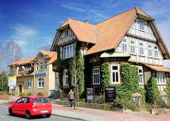 Architektur in Uelzen - Wohnhaus mit Efeu bewachsen - SPD Haus, rotes Auto; dahinter das Gebäude der Polizei.