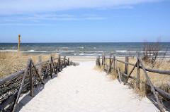 Mit einem Holzzaun abgesperrter Sandweg durch die Dünen zum Strand der Ostsee bei Łeba, Polen.