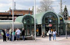 Moderner Eingang vom Bahnhof Uelzen - Passanten und Fahrgäste; im Hintergrund das historische Bahnhofsgebäude, das 2000 nach Plänen des österreichischen Künstlers Friedensreich Hundertwasser umgebaut wurde.