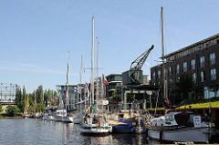 Sportboote im Stader Hafen - historischer Hafenkran und Wohnhäuser - lks. im Hintergrund das Gasometer, das als Industrieanlage unter Denkmalschutz steht.