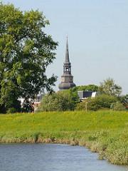 Blick über die Wiesen am Ufer der Schwinge zum Kirchturm der Kirche Kirche Ss. Cosmae et Damiani in Stade.