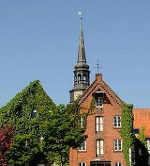 Historische Speicher mit Efeu bewachsen am Hafenrand von Stade - Kirchturm der St. Cosmaekirche.