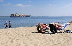 Elbufer bei Stade / Containerschiff auf der Elbe - Strandbesucher in Liegen / Liegestühle im Sand in der Sonne - Spaziergänger.