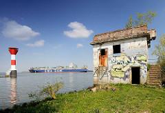 Elbufer beim Stader Sand - altes Gebäude mit Graffiti; Leuchtfeuer und Frachtschiff auf der Elbe.