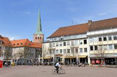 Herzogenplatz in Uelzen - ein Fahrradfahrer fährt über den leeren Platz - Aussengastronomie, Tische in der Sonne am Rande des Platzes - im Hintergrund der Kirchturm der St. Marienkirche.