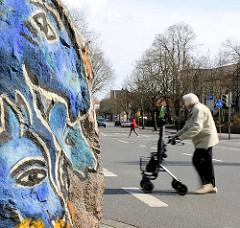 Ausschnitt eines bunt bemalten Felsbrocken - Steinskulpturen der Künstlerin Dagmar Glemme; Frau mit Rollator überquert die Strasse.
