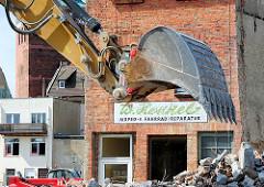 Abriss von Gebäuden in der Mühlenstrasse - Abrissbagger und Bauschutt. Baggerschaufel und Firmenschild eines Abrissgebäudes - W. Henkel Moped Fahrrad Reparaturen.