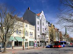 Mehrstöckige Wohngebäude an einer Hauptstrasse in Uelzen - Gründerzeit Etagenhaus mit fliederfarbenen Fassade - Bus der öffentlichen Verkehrsmitte.