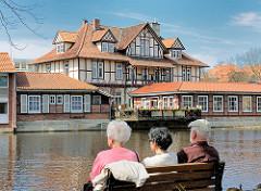 Frühlingstag am Ratsteich, der aufgestauten Ilmenau in Uelzen - Parkbesucher sitzen auf einer Bank in der Sonne am Wasser - auf der gegenüber liegendes Seite des Teichs ein Fachwerkgebäude mit Aussengastronomie an der Ilmenau.
