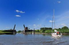 Segelboot unter Motor auf der Schwinge - Schwingesperrwerk, geöffnete Klappbrücke, blauer Himmel.