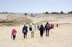 Lontzkedüne im polnischen Slowinzischen Nationalpark bei Leba - Gruppen von Touristen wandern durch den Sand Richtung Ostsee.
