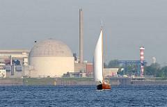 """Das Kernkraftwerk am Elbufer bei Stade wurde 1972 in Betrieb genommen und 2003 stillgelegt. Seitdem wird es """"zurückgebaut"""" - rechts das Leuchtfeuer am Stader Sand; ein Segelschiff kreuzt auf der Elbe."""