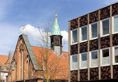 Dach und Glockenturm der Heiligen Geistkapelle in Uelzen - 1320 als Bestandteil des Heiligen Geist Hospitals erbaut. Rechts Fassade eines Geschäfsgebäude - Bürogbäudes, Achitekur der 1970er Jahre.