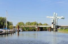 Blick über die Schwinge zur Klappbrücke der L111 / Buxtehuder Strasse; Sportboote am Ufer.