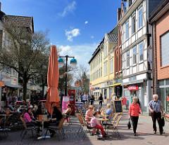 Frühlingstag in der Sonne - Eiscafé mit Tischen in einer Fussgängerzone von Uelzen.