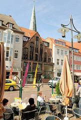 Eiscafé am Strassenrand - Tische mit Gästen in der Sonne; im Hintergrund das im Mittelalter errichtet Gildhaus und die Turmspitze der St. Marienkirche.