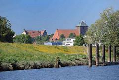 Ufer der Schwinge mit Deich - Dalben am Ufer; Blick zur gotischen Kirche St. Wilhadi in Stade.