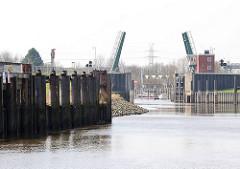Geöffnete Klappbrücke über die Schwinge bei Brunsdorf - Eisendalben am Ufer des Flusses der durch Stade fliesst.