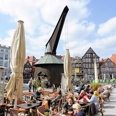 Sonnentag in Stade - Café mit Tischen und Sitzplätzen auf dem Fussweg - historischer Holztretkran / Alter Kran am historischen Hansehafen.