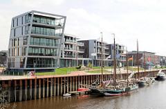 Historische Ewer im Hafen Stades - mehrstöckige Wohnhäuser am Hafen.