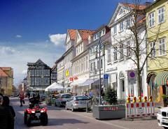 Bilder aus Uelzen - mehrstöckige Geschäftshäuser / Wohnhäuser in der Gudestrasse - en rotes Quad, All Terrain Vehicle auf der Strasse.