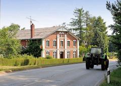 Wohnhaus eines Bauernhofs an der Lübecker Strasse in Ammersbek - ein Traktor fährt auf der Landstrasse.