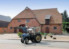 Ein Traktor / Trecker mit angekoppeltem Heuwender auf der Dorfstrasse in Bünningstedt, Gemeinde Ammersbek - im Hintergrund ein landwirtschaftliches Gebäude; Scheune.