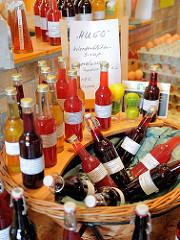 Flaschen mit Holunderblütensirup in einem Korb - Hofladen in Bünningstedt; Gemeinde Ammersbek.