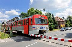 Der AKN Zug Richtung Elmshorn überquert die Mühlenstrasse in Barmstedt - die Schranken sind heruntergelassen, Autos warten.