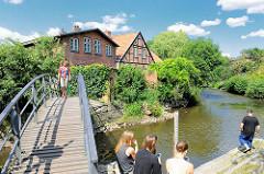 Fussgängerbrücke über die Trave - Jugendliche sitzen am Flussufer in Bad Oldesloe, Kreis Stormarn.
