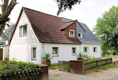 Zweifamilienhaus mit Jägerzaun und Holztor; unterschiedliche Dachpfannen - Siedlung Daheim; Ahrensburg - Ammersbek; Metropolregion Hamburg.