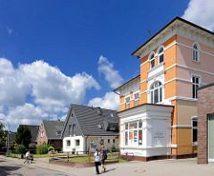 Alte und neue Architektur an der Marktstrasse in Barmstedt, Kreis Pinneberg - Gründerzeitgebäude und Einzelhäuser mit Spitzdach, Fussgänger.