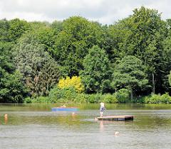 Rantzauer See in Barmstedt - Tretboot und Badende, hohe Bäume am Ufer vom See.