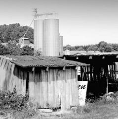 Alter Holzschuppen mit Wellblechdach - im Hintergrund ein Getreidesilo - Schwarz Weiss SW Aufnahme; Bilder aus der Gemeinde Ammersbek / Ortsteil Bünningstedt.