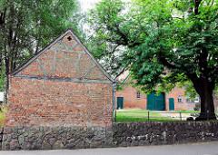 Fachwerkkate mit Ziegelsteinen - Steinmauer; im Hintergrund Gebäude eines Bauernhofs - Dorfstrasse Bünningstedt, Gemeinde Ammersbek.