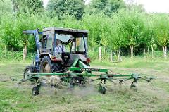 Heuernte auf einer Wiese in Bünningstedt / Ammersbek - ein Landwirt wendet mit seinem Traktor und dem Heuwender das gemähte Gras.