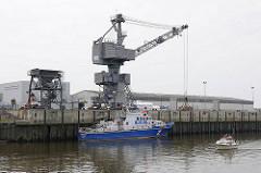 Hafen Glückstadt - Hafenkran an der Kaimauer - das Hamburger Polizeiboot HERBERT WEICHMANN hat an der Kaimauer festgemacht - ein Sportboot von der Elbe kommend läuft in den Glückstädter Hafen ein.