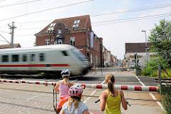 Bahnübergang mit heruntergelassener Bahnschranke an der Bahnhofstrasse in Glückstadt - ein Zug fährt vorüber Kinder warten mit ihrem Fahrrad vor der Schranke - im Hintergrund die Große Kremper Strasse.