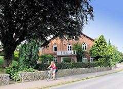 Dicht belaubte Blutbuche / Rotbuche im Vorgarten eines Wohnhauses auf in dem Dorf Bünningstedt, Ammersbek; Steinmauer aus Feldsteinen an der Dorfstrasse - Radfahrerin in Fahrt.
