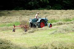 Historischer Traktor Eicher Diesel, luftgekühlt - Baujahr ca. 1950; der Traktor zieht einen alten Heuwender auf einer Wiese am Rand des Rantzauer Forst in Barmstedt, Kreis Pinneberg - Schleswig Holstein.