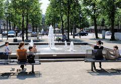 Sprudelnder Brunnen - Zentrum von Ahrensburg, Kreis Stormarn. Familien sitzen in der Sonne auf Bänken am Brunnenbecken.